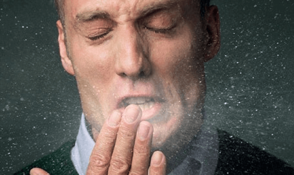 Man covering his mouth while he sneezes and mucus particulates go into the air.