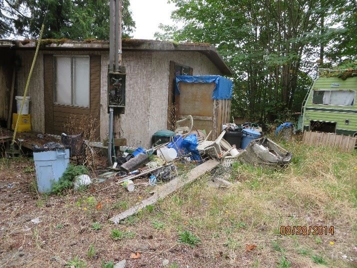 Trash along side house at Highway 101 property before successful cleanup